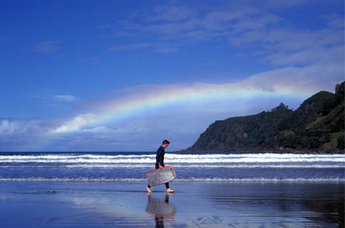 East coast, Ruatoria maori most habbited town.Tuparoa Bay with rainbow Man with ski board. New Zealand, Australasia ©Maro Kouri/IML Image Group