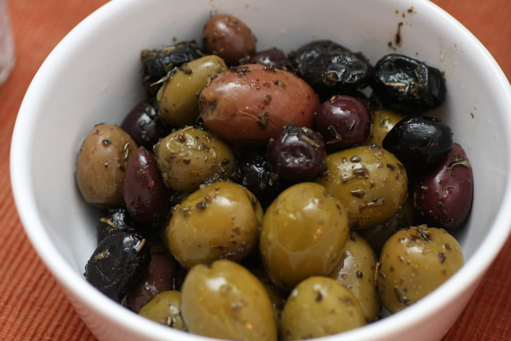Assorted olives with olive oil and herbs